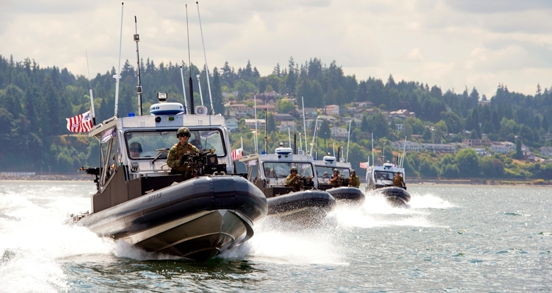 Boat crews from Coast Guard Port Security Unit 313in Everett, Wash., conduct high-speed boat maneuvers and safety zone drills during an exercise at Naval Station Everett July 22, 2015. The exercise was held in an effort to fine tune their capabilities in constructing and running entry control points, establishing perimeter security, and maintaining waterside security and safety zones.