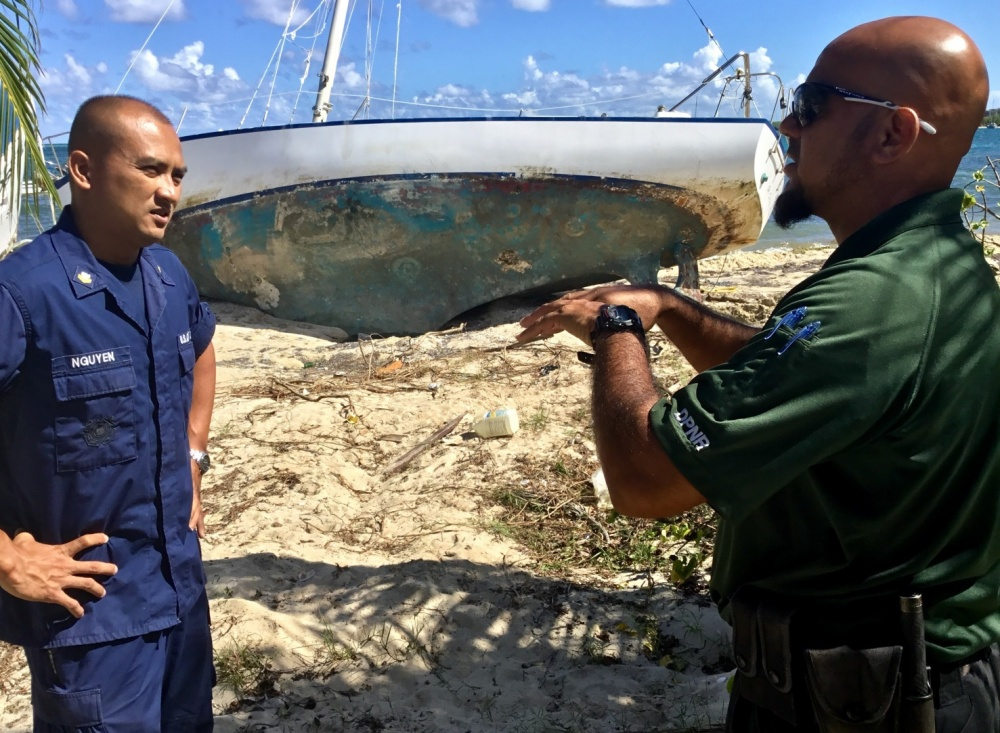 Deployed Reservist Petty Officer 2nd Class Ky Nguyen speaks to a boat owner during a vessel inspection.