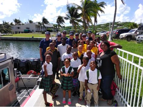 Deployed Coast Guard members pose with at-risk youth from Project Promise after providing a tour of Coast Guard small response boats